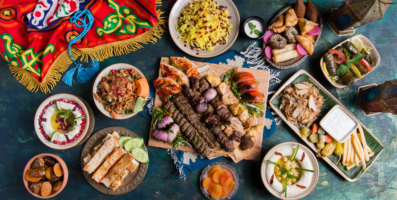 Kebab platter, shish tawook, shawarma platter, vine leaves, fatayer, fattoush salad, moutabbel, dates, manosuhe, apricots, hummus, lanterns, for ramadan, on a green background